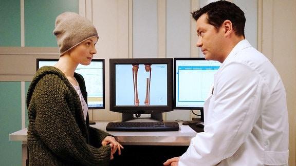 Dr. Philipp Brentano (Thomas Koch) sagt Luka Ostberger (Nathalie Thiede), dass es neben der Amputation ihres Unterschenkels eine weitere erfolgversprechende OP-Methode gibt.