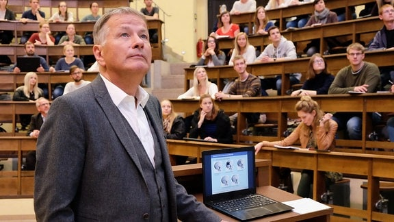 Dr. Roland Heilmann (Thomas Rühmann) hält vor Studenten der medizinischen Fakultät einen Vortrag.