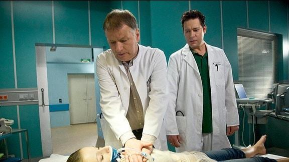 Laura liegt im hypoglykämischen Koma. Dr. Heilmann versucht, sie wiederzubeleben. Dr. Philipp Brentano  steht hinter ihm.