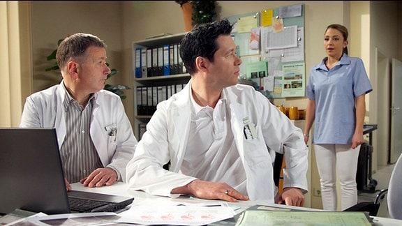 Arzu kommt in einen Raum, in dem Roland Heilmann und Philipp Brentano eine Operation besprechen. Brentano verhält sich ihr gegenüber kühl und sachlich.
