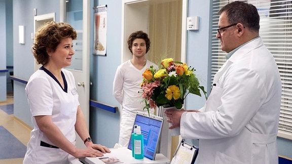 Hans-Peter Brenner (Michael Trischan, re.) hat von einer Patientin als Dankeschön Blumen geschickt bekommen. Schwester Ulrike (Anita Vulesica, li.) merkt, dass er sich über die Geste freut, aber mit den Blumen nicht so recht etwas anzufangen weiß.