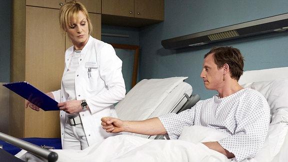 Dr. Lea Peters (Anja Nejarri) will gerade das Zimmer verlassen, als Jenne Derbeck (Patrick Kalupa) nach ihr greifen will.