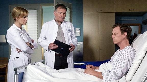 Dr. Lea Peters (Anja Nejarri, li.) hat tatsächlich ein Hirn-Aneurysma bei Jenne Derbeck (Patrick Kalupa, re.) entdeckt. Dies muss dringend operiert werden, da es jederzeit platzen könnte. Da Jenne Lea für seine Traumfrau hält, hat sie Dr. Roland Heilmann (Thomas Rühmann, mi.) um Hilfe gebeten.