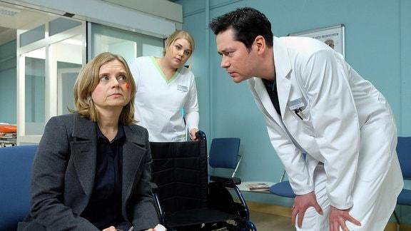 Sylvia Haas (Nina Weniger, li.) kommt mit einer Schnittwunde unter dem Auge, die angeblich von einem heruntergefallenen Bild stammt, in die Sachsenklinik.
