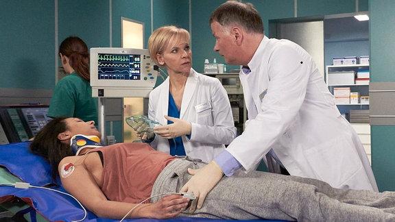 Suleika Lindemann als Alia Jandali (liegend im Bett), Thomas Rühmann als Dr. Roland Heilmann und Andrea Kathrin Loewig als Dr. Kathrin Globisch daneben.