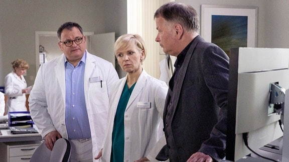 Michael Trischan als Hans-Peter Brenner, Andrea Kathrin Loewig als Dr. Kathrin Globisch und Thomas Rühmann als Dr. Roland Heilmann. Sie stehen nebeneinander und beraten sich.