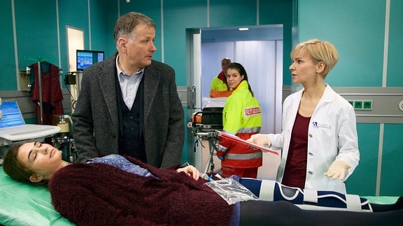 Komparsen als Notarztteam, Natalia Witmer als Tatjana Geiger, Thomas Rühmann als Dr. Roland Heilmann und Andrea Kathrin Loewig als Dr. Kathrin Globisch