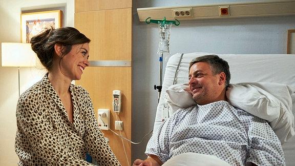 Tina Sievers (Victoria Sordo)  sitzt freudestrahlend am Krankenbett ihres Freundes Joachim Bindel (Rüdiger Klink) .