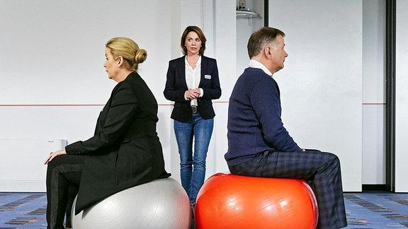 Sarah Marquardt (Alexa Maria Surholt, li.) und Roland Heilmann (Thomas Rühmann, re.) sutzen Rücken an Rücken auf Gymnastikbällen.