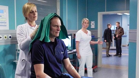 Während sein Kollege Ralf mit einer lebensgefährlichen Schussverletzung operiert wird, hat Jan Fischer (Thorsten Nindel, sitzend) nur eine leichte Kopfverletzung. Dr. Lea Peters (Anja Nejarri, li.) übernimmt die Erstversorgung, will aber zur Sicherheit noch ein CT durchführen.