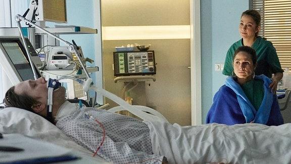 Patricia Noack (Ellenie Salvo Gonzales, re. sitzend) sitzt besorgt am Bett ihres Mannes Ralf (Timo Jacobs, li.) der bei einem Überfall mit Schusswechsel verletzt wurde. Oberschwester Arzu Ritter (Arzu Bazman, re.) bringt ihr eine Decke und versucht, sie damit etwas zu beruhigen.