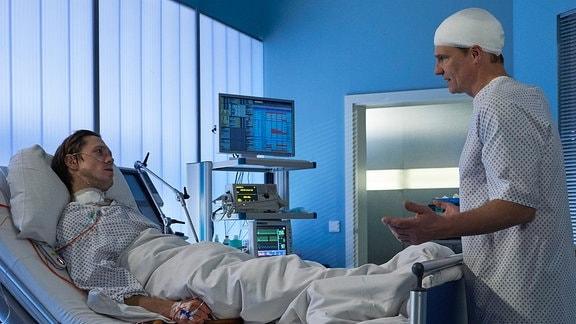 Als Ralf Noack (Timo Jacobs, li.) erwacht, steht Jan Fischer (Thorsten Nindel, re.) an seinem Bett. Jan ist froh, dass es seinem Freund und Kollegen wieder besser geht. Ralf jedoch ahnt, warum Jan wirklich da ist. Er will wissen, ob Ralf sich an den Überfall erinnern kann.