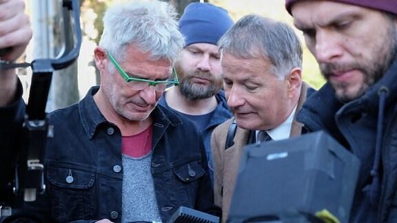 Schauspieler und Regisseur überprüfen eine Aufnahme.