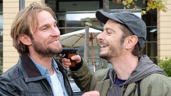 Zwei schauspieler, einer hält dem anderen spaßeshalber eine Requisiten-Pistole an den Hals.