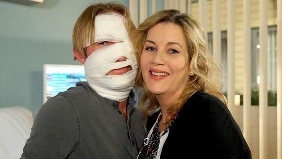 Schauspieler posieren in einer Drehpause, einer mit Verband im Gesicht.