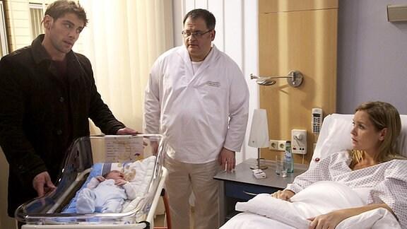 Als Dr. Niklas Ahrend (Roy Peter Link, li.) nach Jasmin Schenk (Judith Hoersch, re.) sieht, fällt ihm auf, dass es ihrem Neugeborenen Kind gar nicht gut geht. Obwohl er kein Arzt an der Sachsenklinik ist, schnappt er sich das Baby und will es sofort untersuchen. Auch von Pfleger Hans-Peter Brenner (Michael Trischan, mi.) lässt Niklas sich nicht aufhalten.
