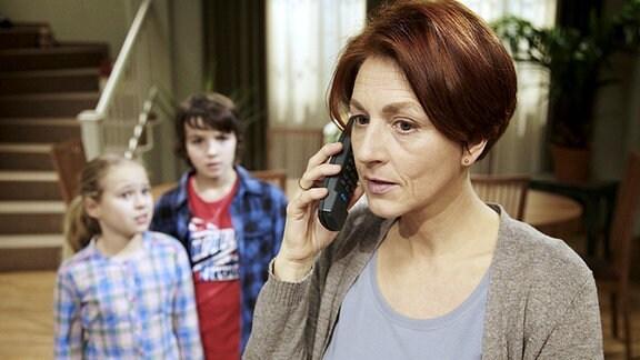 Lisa (Ella Zirzow, li.) hat der besorgten Pia Heilmann (Hendrikje Fitz, re.) gestanden, das Jonas (Anthony Petrifke, mi.) in Englisch versetzungsgefährdet ist und das er, um Pia zu schonen, nichts gesagt hat. Als das Telefon klingelt, ist Jonas' Englischlehrer am Apparat und erzählt Pia von der gefälschten Unterschrift.