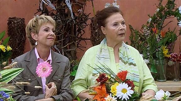 Zwei Frau an einem Tisch voller Blumen
