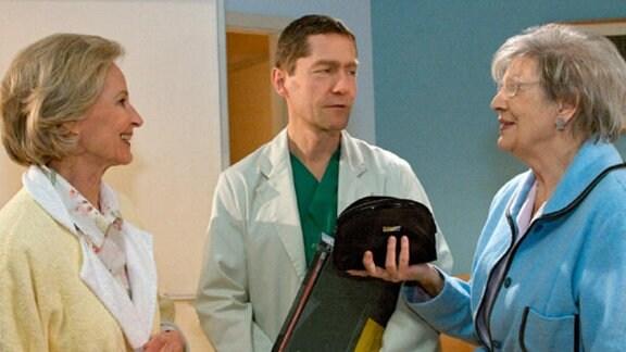 Dr. Kaminski gestattet den Seniorinnen den Besuch bei einer Patientin.