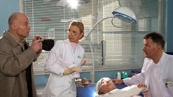 Als Dr. Heilmann Gerda untersucht, zückt ihr Mann den Fotoapparat.