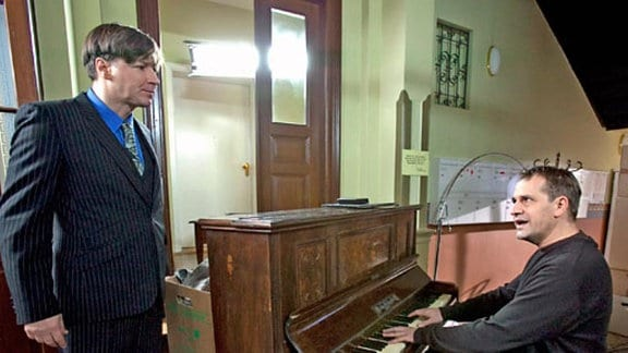 Stefan Merck und Georg Büttner transportieren ein Klavier.