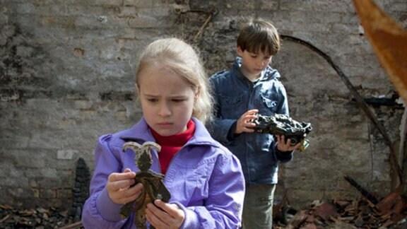 Lisa und Jonas suchen in ihrem abgebrannten Zuhause ihr Spielzeug.