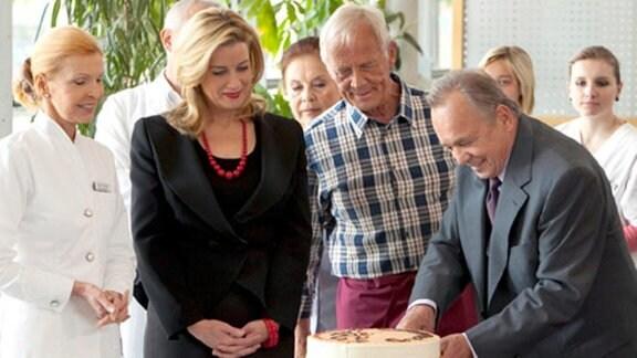 Als Prof. Simoni einen Kuchen anschneiden will, zittert seine Hand.