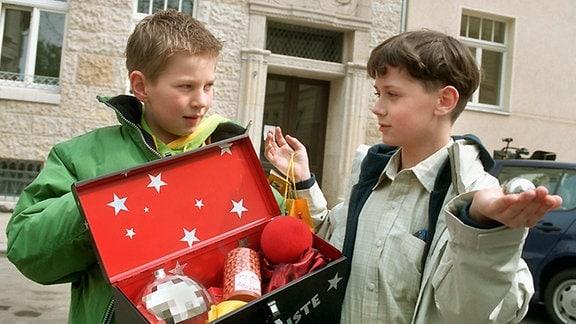 Jakob Heilmann (Karsten Kühn, li.) hält Mario Zimmer (Kevin Leisner) einen Zauberkasten hin.