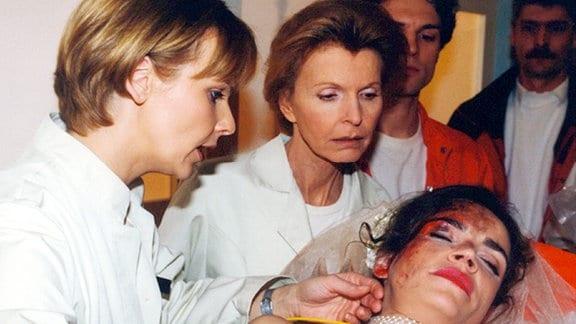 Auf dem Weg zur Trauung geraten die Braut (Rebecca Immanuel) und ihr zukünftiger Schwager in einen Autounfall. Dr. Kathrin Globisch (Andrea Kathrin Loewig, links) und Oberschwester Ingrid (Jutta Kammann) leiten die Behandlung dieser schicksalshaften Fügung ein.