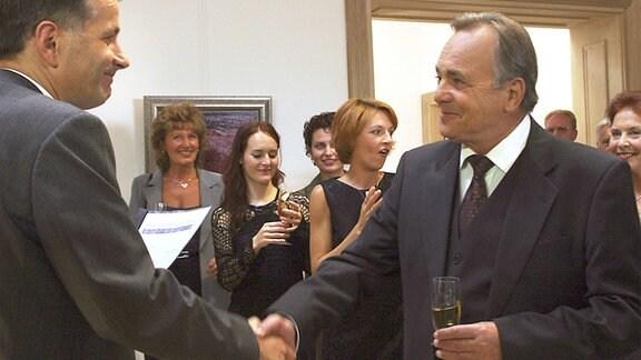 Dr. Heilmann (Thomas Rühmann) gratuliert Prof. Simoni (Dieter Bellmann) zu seinem 60. Geburtstag.