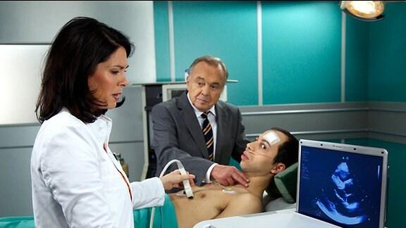 Elena Eichhorn und Prof. Simoni stehen vor einem medizinischen Gerät und wollen der Ursache für die Beschwerden von Benjamin Helbig auf den Grund gehen.