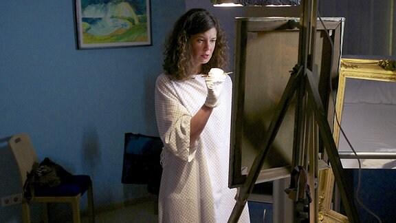 Iris Markgraf will in der Klinik ein Gemälde  fertigstellen. Kurze Zeit später bricht sie unter starken Schmerzen zusammen.
