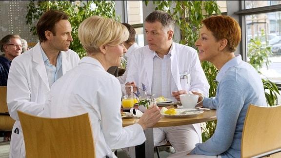 Wenig begeistert, ihre Mittagspause an einem gemeinsamen Tisch verbringen zu müssen, setzen Roland (Thomas Rühmann, 2. v. re.) und Martin (Bernhard Bettermann, 1. v. li.) ihr Streitgespräch aus dem OP-Vorbereitungsraum fort. Schafft es Martin doch noch, Roland von den Vorteilen einer privaten Finanzierung der Sachsenklinik zu überzeugen? Eine freundschaftliche Wiederannäherung lassen die beiden jedenfalls - trotz hartnäckiger Versuche von Kathrin (Andrea Kathrin Loewig, 2. v. li.) und Pia (Hendrikje Fitz,1. v. re.) - nicht zu.