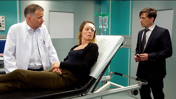 Dr. Roland Heilmann (Thomas Rühmann, li.) mit einer Patientin und deren Ehemann