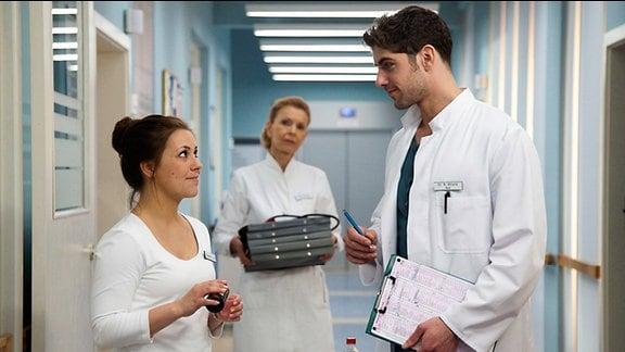 Schwester Julia (Sarah Tkotsch, li.) flirtet mit Dr. Niklas Ahrend (Roy Peter Link, re.). Sie werden von Oberschwester Ingrid (Jutta Kammann, mi.) beobachtet
