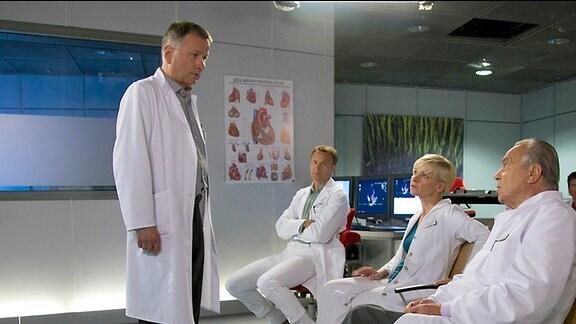 Dr. Roland Heilmann (Thomas Rühmann, li.) benötigt den Rat seiner Kollegen Prof. Simoni (Dieter Bellmann, re.), Dr. Kathrin Globisch (Andrea Kathrin Loewig, 2.v.re.) und Dr. Martin Stein (Bernhard Bettermann, 3.v.re.)