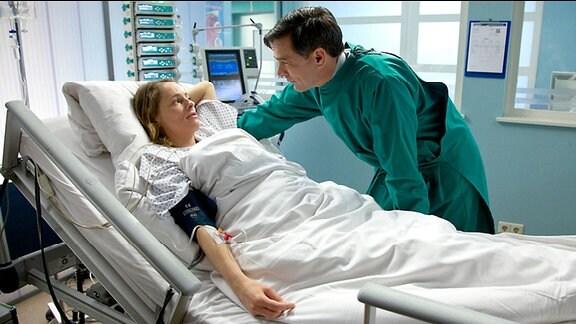 Patientin Kerstin (Rike Schäffer) liegt im Krankenbett. Ihr Mann Oliver Heller (Wolfgang Krewe) redet auf sie ein
