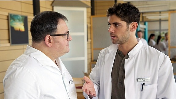 Pfleger Hans-Peter Brenner (Michael Trischan, li.) hat mitbekommen, dass seine Kollegin Schwester Julia mit Dr. Niklas Ahrend (Roy Peter Link, re.) verabredet ist