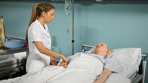 Als Schwester Arzu (Arzu Bazman, li.) nach Corinna Lehmann (Anne Müller, re.) sieht, liegt diese völlig benommen und fast nicht ansprechbar im Bett.