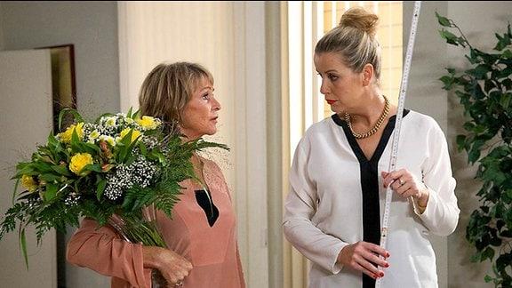 1_Barbara Grigoleit (Uta Schorn, li.) mit einem Blumenstrauß und  Sarah Marquardt (Alexa Maria Surholt, re.) mit einem Zollstock.