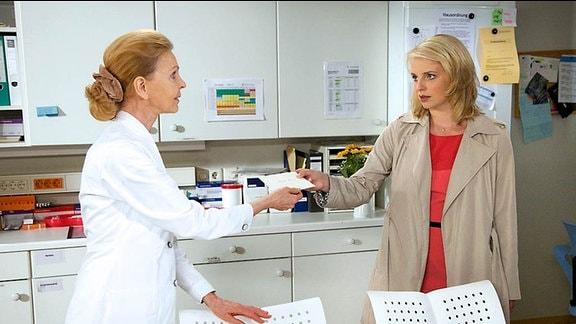 5_Patrizia Schott (Anja Boche, re.) überreicht Oberschwester Ingrid (Jutta Kammann, li.) einen Brief.