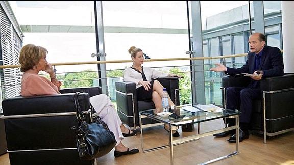 6_Sarah Marquardt (Alexa Maria Surholt, mi.),  Dr. Wolfgang Berger (Horst Günther Marx, re.), und Barbara Grigoleit (Uta Schorn, li.) sitzen in Ledersesseln.