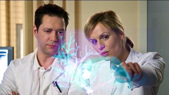 Dr. Lea Peters (Anja Nejarri) erklärt Dr. Philipp Brentano (Thomas Koch) eine OP anhand eines virtuellen Models