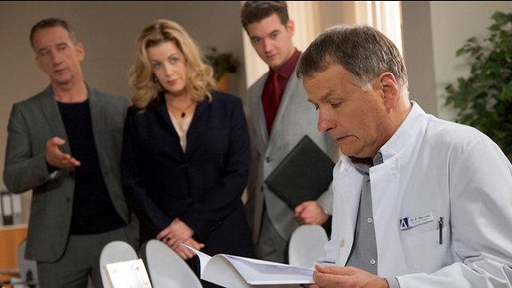 Klinikleiterin Sarah Marquardt, Abaris-Chef Alexander Weber und Sarahs Assistent Clemens Manthey warten auf eine Reaktion von Chefarzt Dr. Roland Heilmann.
