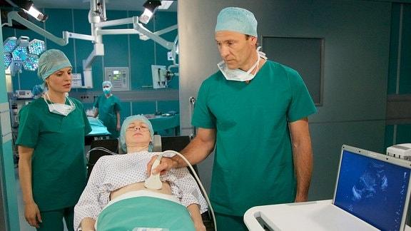 Dr. Martin Stein (Bernhard Bettermann, re.) operiert Birgit Jasper (Aline Staskowiak, mi.). Dr. Lea Peters (Anja Nejarri, li.) wird Martin bei der Not-OP unterstützen.