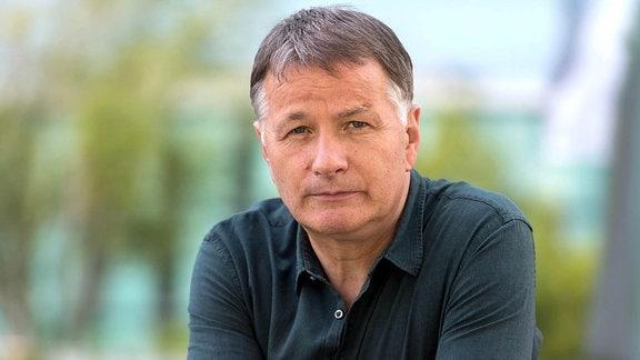 Ein Mann blickt ernst in die Kamera. Thomas Rühmann ist als Dr. Roland Heilmann in den Folgen 35 und 36 zu Gast im Johannes-Thal-Klinikum