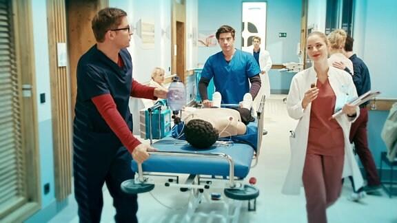 Ärzte schieben einen Patienten auf einem Bett durch ein Krankenhaus.