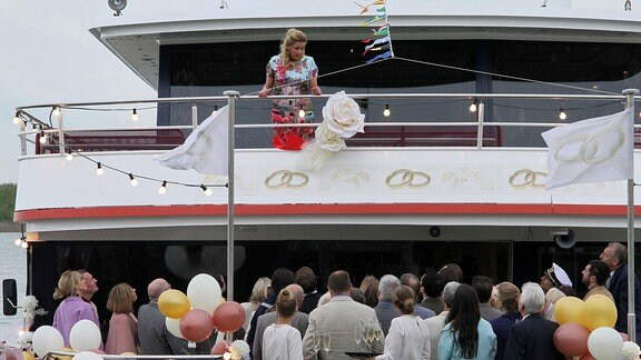 Sarah Marquardt (Alexa Maria Surholt, oben) versucht, in Absprache mit Kathrin Globisch, aus der Situation das Beste zu machen und so wird aus der geplatzten Hochzeit das Sommerfest der Sachsenklinik. Die Gäste sind begeistert.