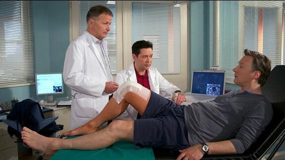 Dr. Heilmann untersucht das Knie eines Patienten.