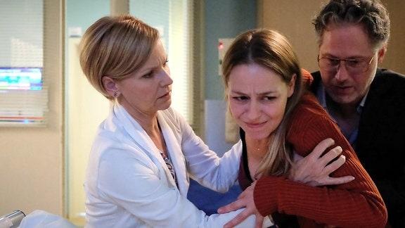 Eine Patienten mit Schmerzen wird von Dr. Globisch gestützt.